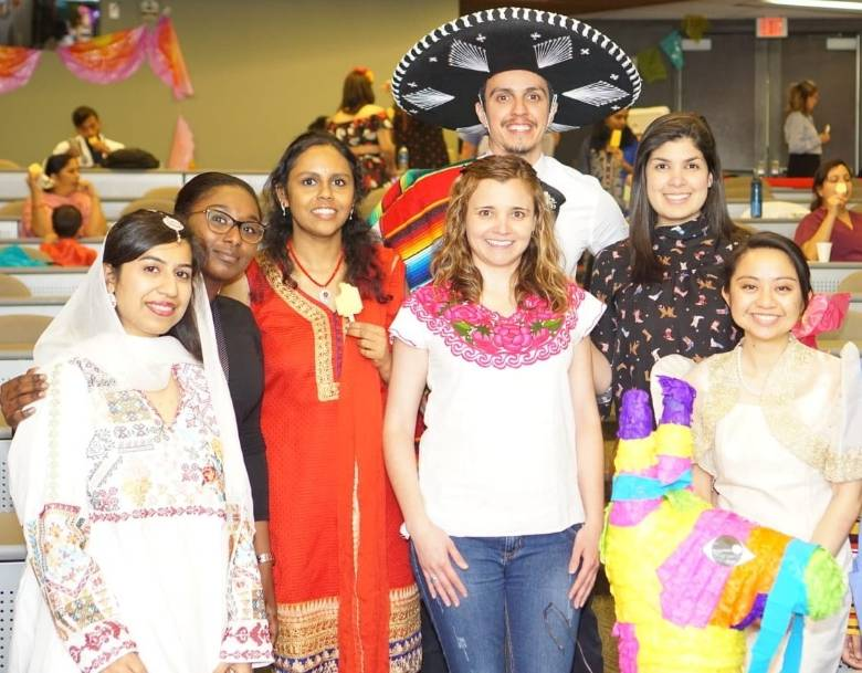 International residents dressed in clothing representative of their cultures.