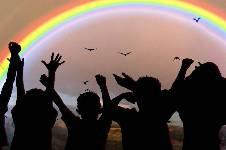 Silhouette of children cheering infron of a rainbow sunset.